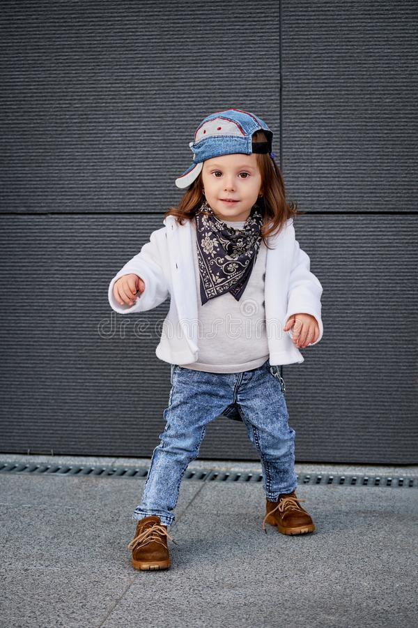 Fashion baby girl hip hop.a little girl in a baseball cap. Portrait of a cute little girl in fashionable clothes.model child hip-hop.little baby girl in the royalty free stock photography
