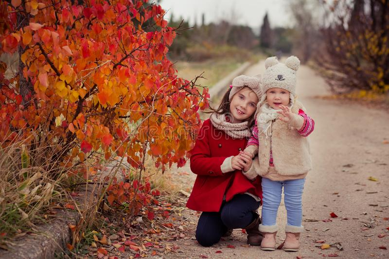 Fashion baby girls sisters stylish dressed brunnette and blond wearing warm autumn clothes jackets posing happy together in colour royalty free stock photography