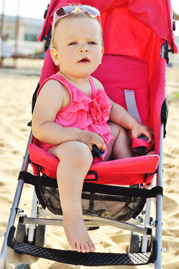 Fashion baby on the sea. In stroller stock image