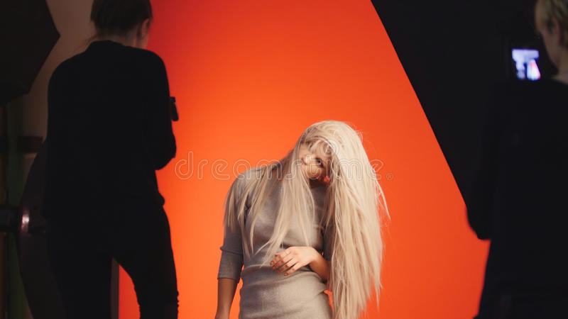 Fashion backstage: blonde girl model plays long hair - photographer take a picture in studio. Red background royalty free stock photos