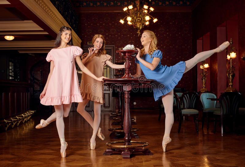Fashion ballerinas in colourful dresses want to taste a sweet meringue and zephyr royalty free stock photos