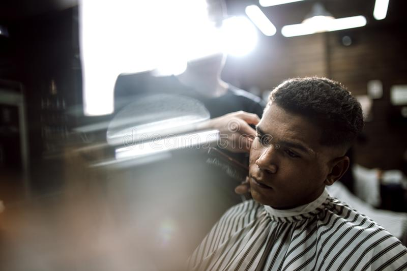 The fashion barber in black clothes makes a razor cut hair for a stylish black-haired man sitting in the armchair in a royalty free stock photo