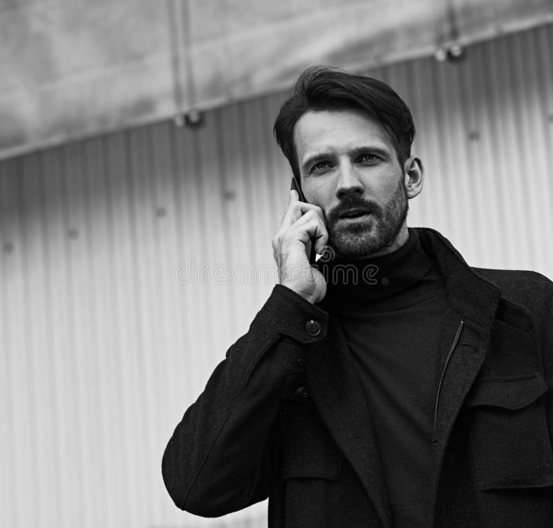Fashion beard style business handsome male model in style clothing blue jacket and speaking on mobile phone on street wall royalty free stock photos