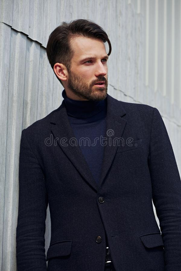 Fashion beard style business handsome male model posing in style clothing blue jacket on street wall outdoors background. Closeup royalty free stock image