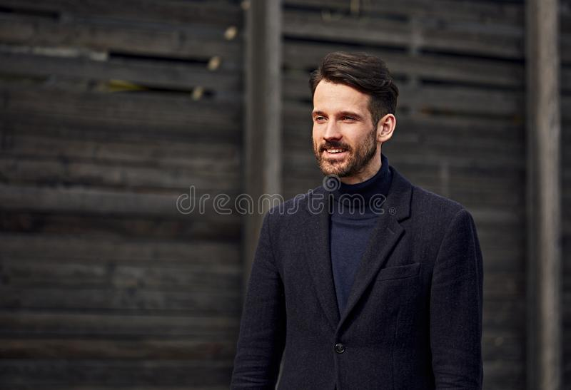 Fashion beard style business handsome male model posing in style clothing blue jacket and trousers on street wooden wall outdoors royalty free stock photo