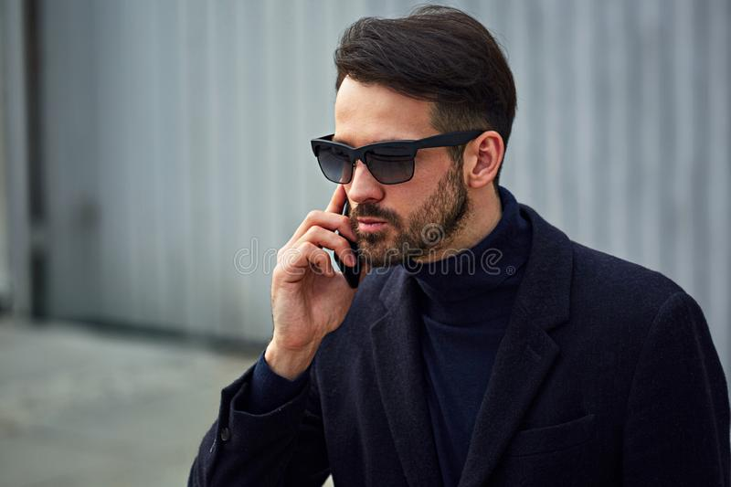 Fashion beard style business handsome male model in fashion sunglasses and blue coat with serious concentrated look talking on stock images