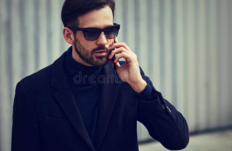 Fashion beard style business handsome male model in fashion sunglasses and blue coat with serious concentrated look talking on royalty free stock images