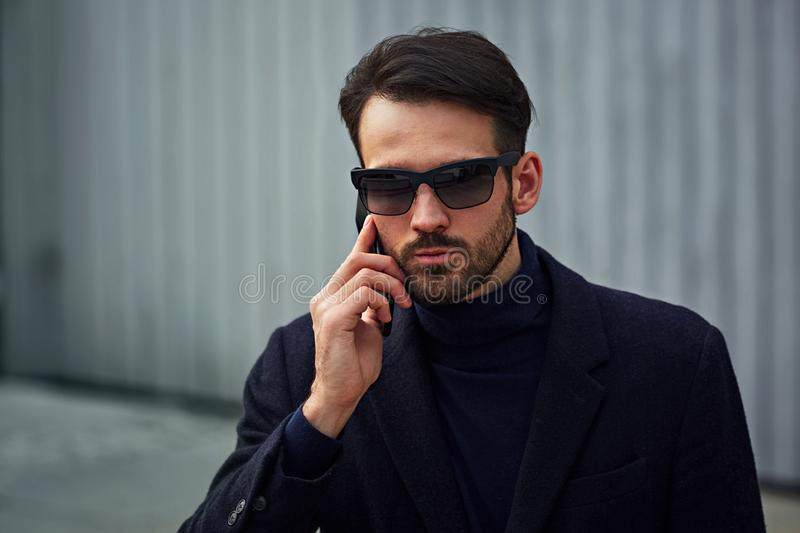 Fashion beard style business handsome male model in fashion sunglasses and blue coat with serious concentrated look talking on stock photo