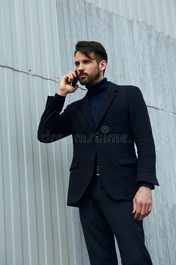 Fashion beard style business handsome male model working and calling on mobile phone in style clothing on street wall outdoors royalty free stock image