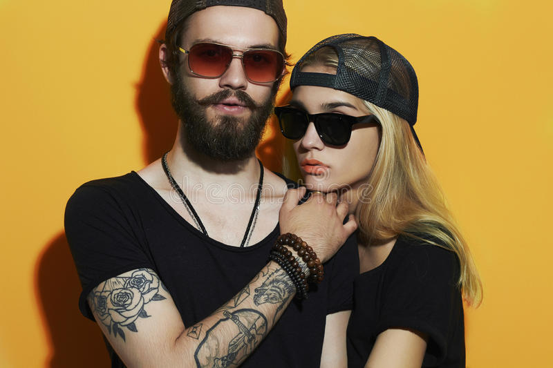 Fashion beautiful couple together. Tattoo Hipster boy and girl. Bearded young men and blonde in sunglasses.Yellow background