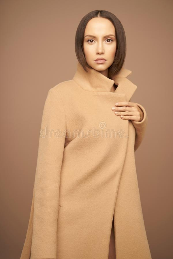 Fashion beautiful lady in beige coat royalty free stock images