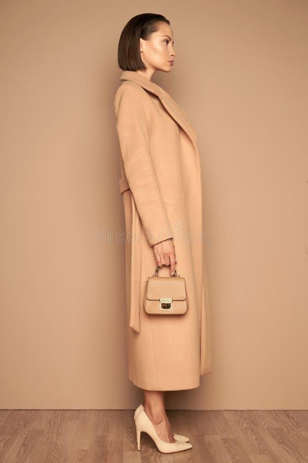 Fashion beautiful lady in beige coat stock photo