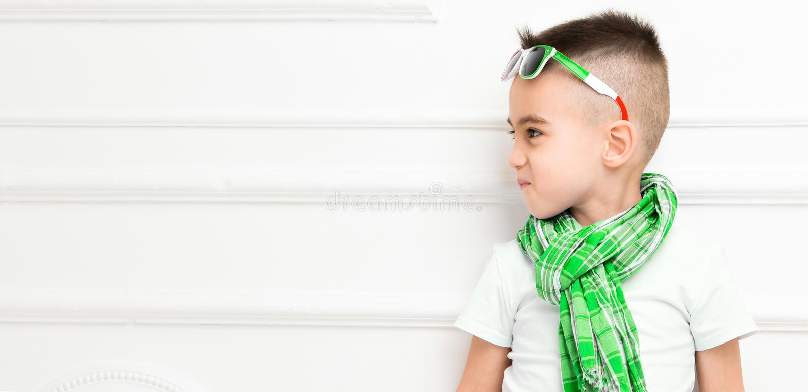 Fashion beautiful little boy in bright pants and t-shirt and scarf royalty free stock photo