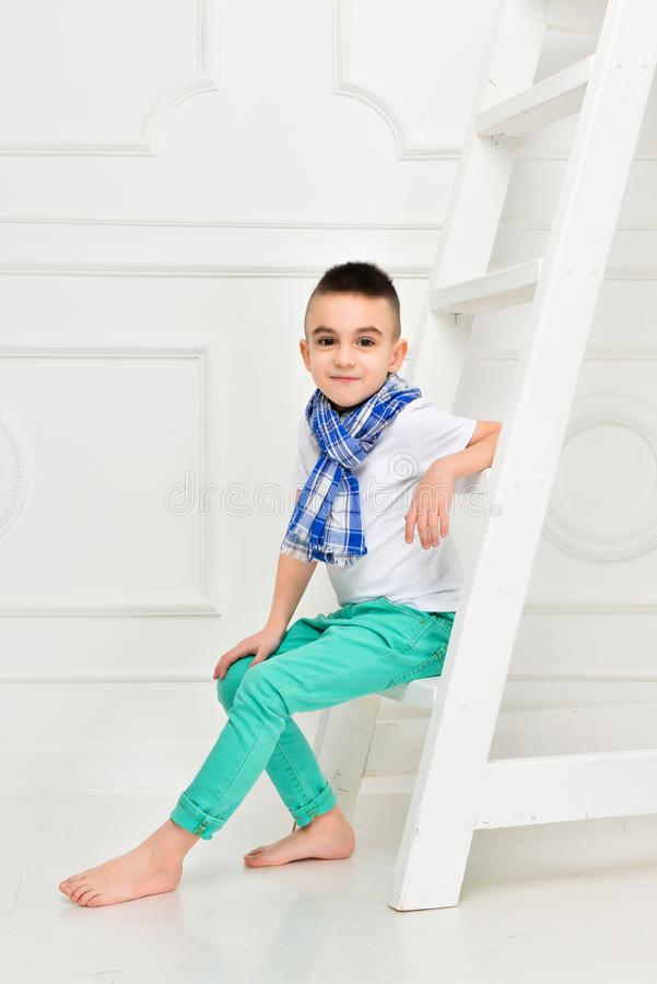 Fashion beautiful little boy in bright pants and t-shirt and scarf royalty free stock images