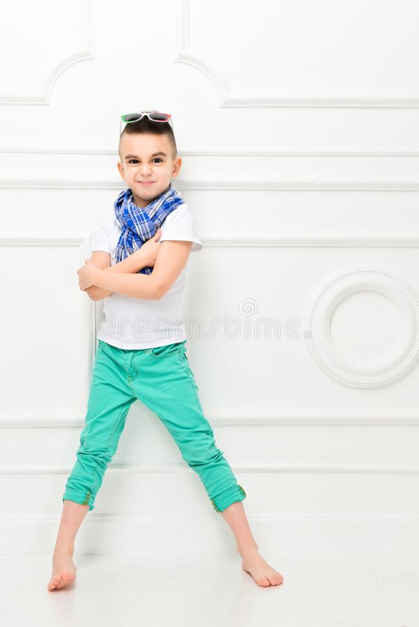 Fashion beautiful little boy in bright pants and t-shirt and scarf royalty free stock image