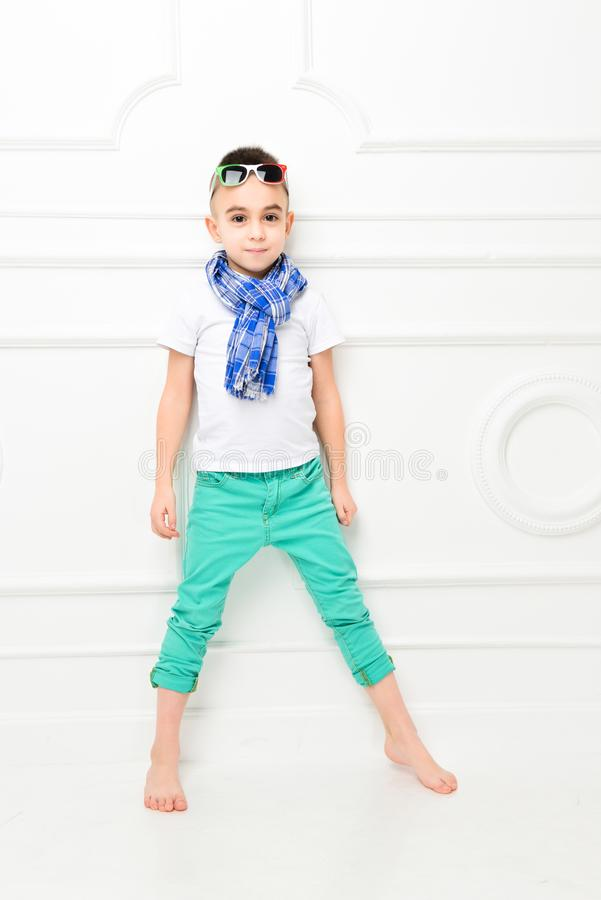 Fashion beautiful little boy in bright pants and t-shirt and scarf stock images