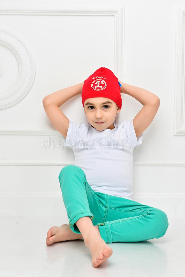 Stylish little boy in a red hat and jeans on a white background in the studio. Fashionable children royalty free stock photography