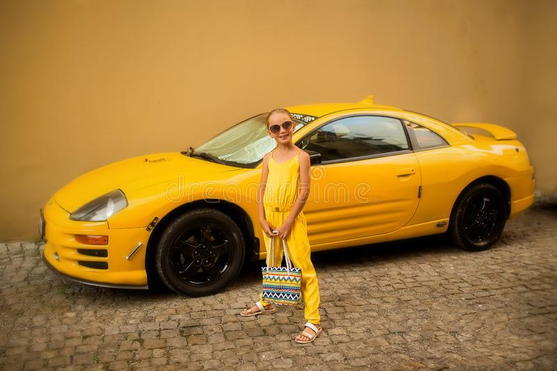 Fashion beautiful little girl in sunglasses on a background of yellow, luxury sports cars royalty free stock photography