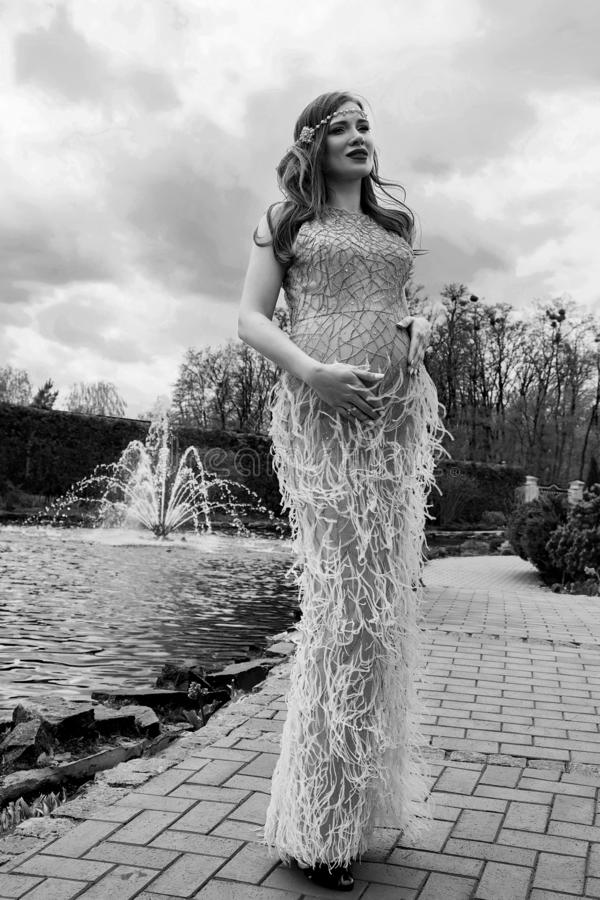 Fashion beautiful pregnant woman walk in the park street in long maxi dress for party wedding fountain waterworks evening dress stock images