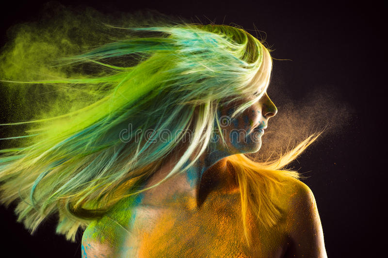Fashion beautiful woman with colorful hair in paint Holi stock images