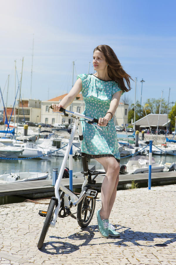 Fashion beautiful woman have fun. The girl in a polka dot dress with a bike on the seafront with yachts. Vertical royalty free stock photos