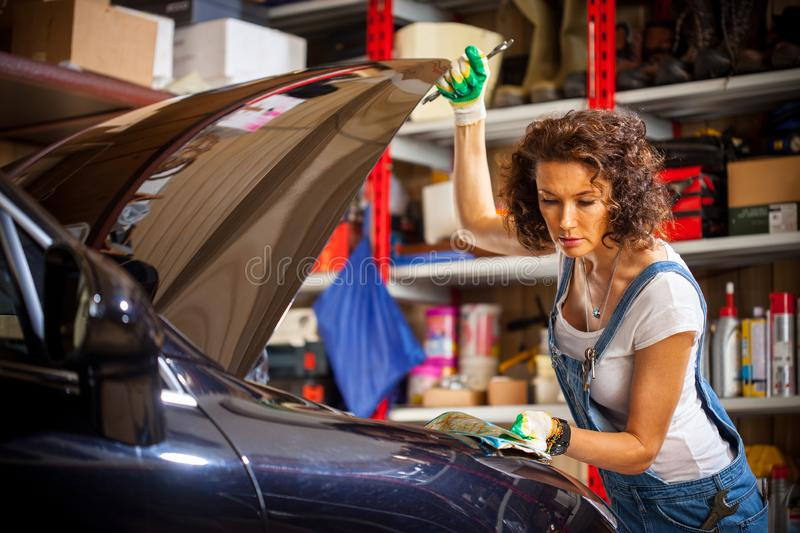 Beautiful woman in the jumpsuit of an auto mechanic stock photo