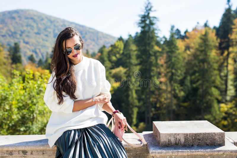 Fashion beautiful woman portrait wearing sunglasses, white sweater and green skirt. With forest trees in the back. Shallow depth of field stock photo
