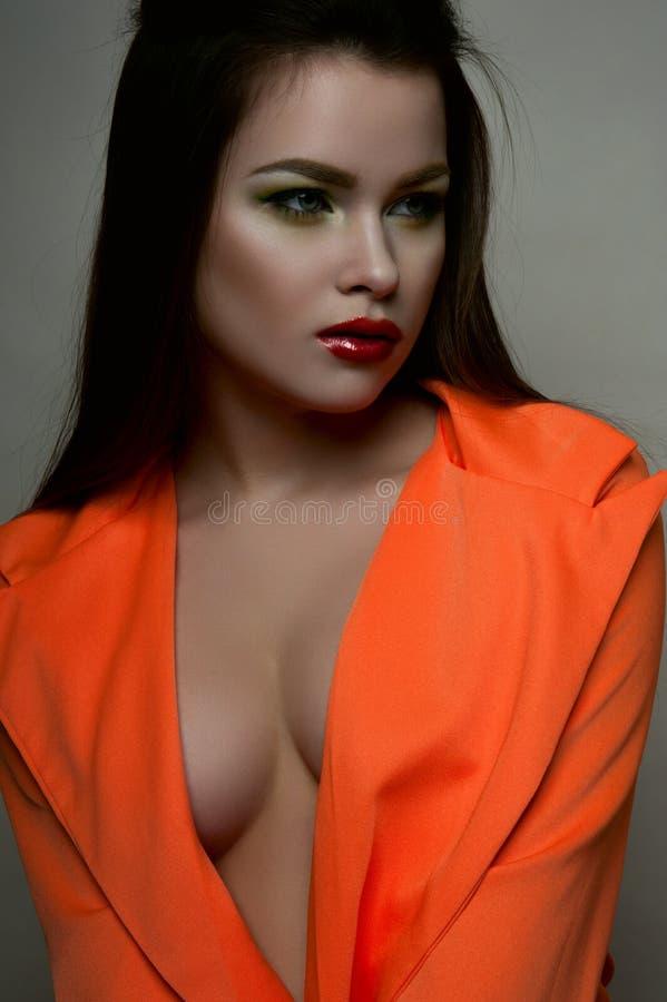 Fashion beauty female model with big breasts in orange jacket royalty free stock image