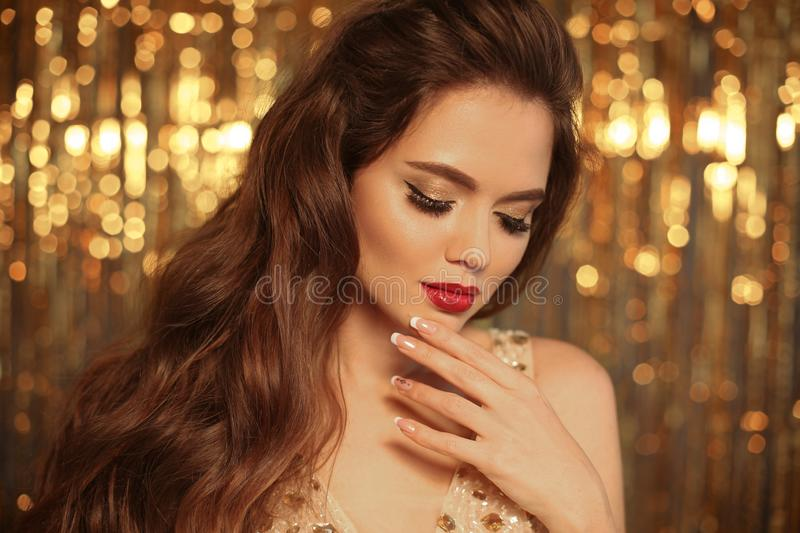 Fashion Beauty Girl Portrait on golden Christmas glitte. Ring bokeh lights background. Glamour Makeup. Gold Jewelry. Hairstyle. Alluring brunette with sensual stock photography