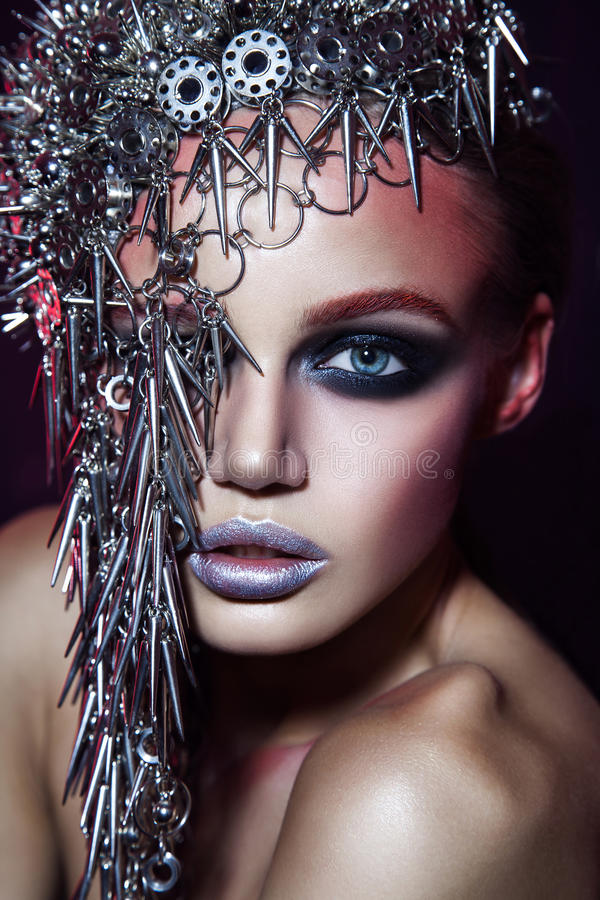 Fashion beauty model with metallic headwear and shiny silver red makeup and blue eyes and red eyebrows on black background.  royalty free stock images