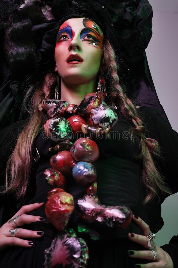 Fashion, beauty, people and halloween concept: Young woman with a bright creative make-up and a big black headdress. royalty free stock image