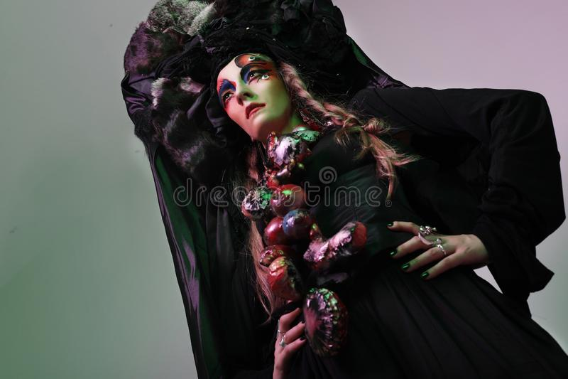 Fashion, beauty, people and halloween concept: Young woman with a bright creative make-up and a big black headdress. stock image