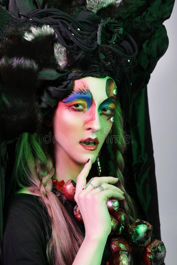 Fashion, beauty, people and halloween concept: Young woman with a bright creative make-up and a big black headdress. royalty free stock images