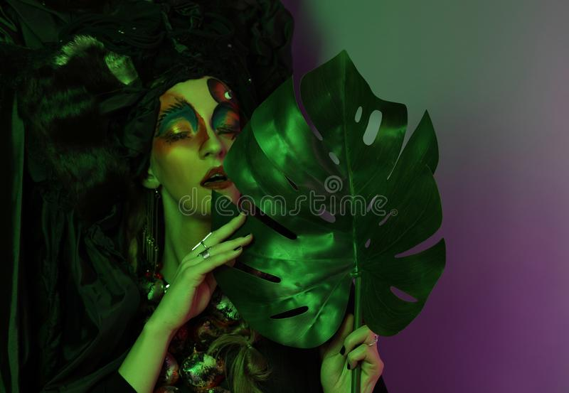 Fashion, beauty, people and halloween concept: Young woman with a bright creative make-up and a big black headdress. royalty free stock photography