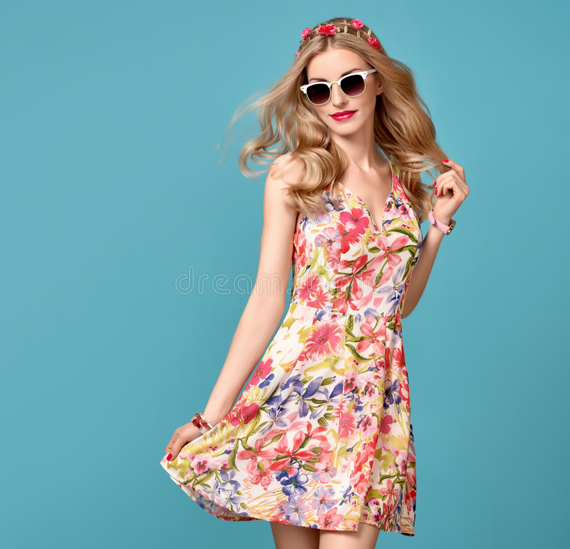Fashion Beauty. Sensual Blond Model. Summer Outfit. Fashion Beauty. Sensual Blond Model in fashion pose Smiling. Woman in Summer Outfit. Trendy Floral Dress stock photo