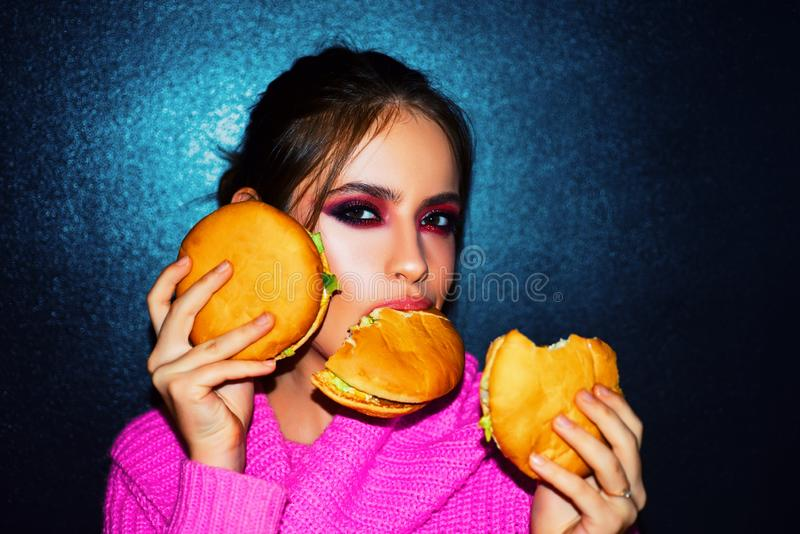 Fashion, beauty.Sexy woman with perfect makeup eating hamburgers. Female beauty visage concept. royalty free stock image