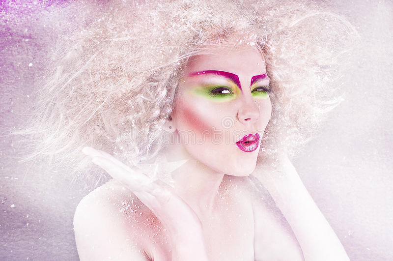 Fashion beauty woman with colorful makeup and creative hairstyle. Covering snowy background stock photos