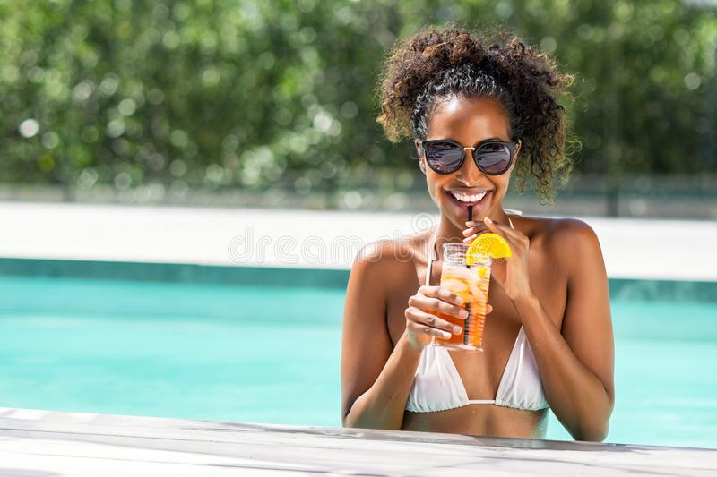 Fashion beauty woman in pool drinking cocktail royalty free stock images
