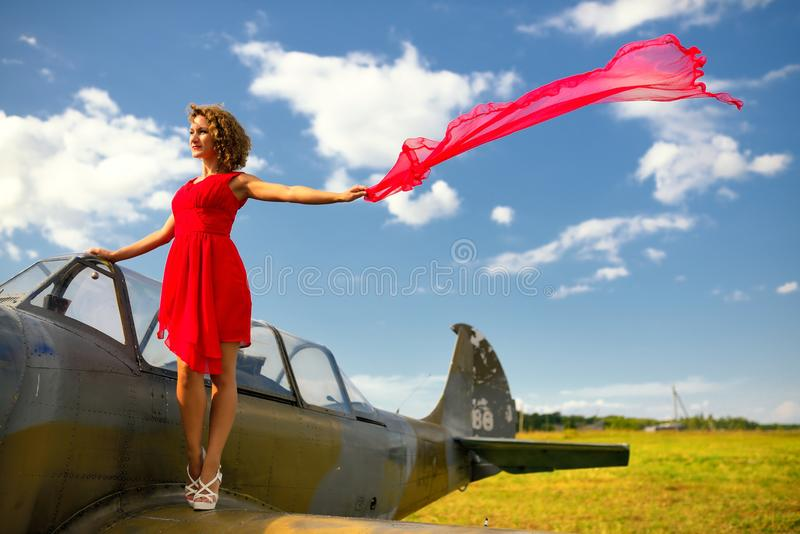 Fashion beautyful woman in red dress stays on a wing of the old plane royalty free stock image