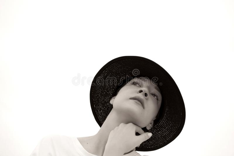 Fashion black and white portrait of a girl with a black hat stock photo