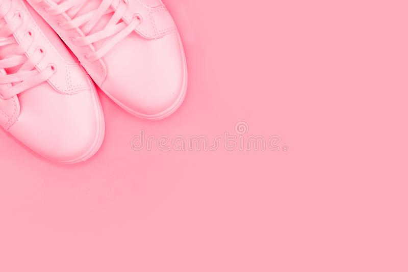Fashion blog or magazine concept. White female sneakers on pink background. Flat lay, top view minimal background.  royalty free stock photos