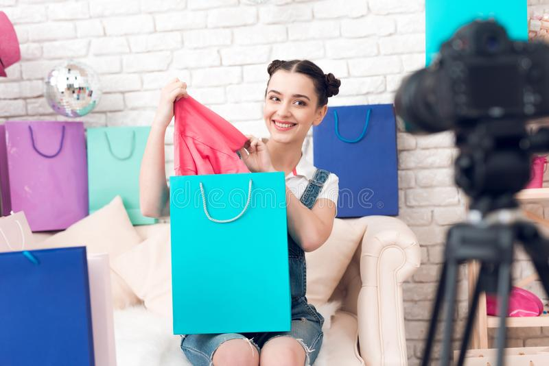 Fashion blogger girl with make up pulls item from colorful bag to camera. royalty free stock photos