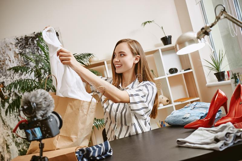 Fashion blogger. Happy and cute woman showing new white shirt on camera while recording new video for her fashion blog. royalty free stock image
