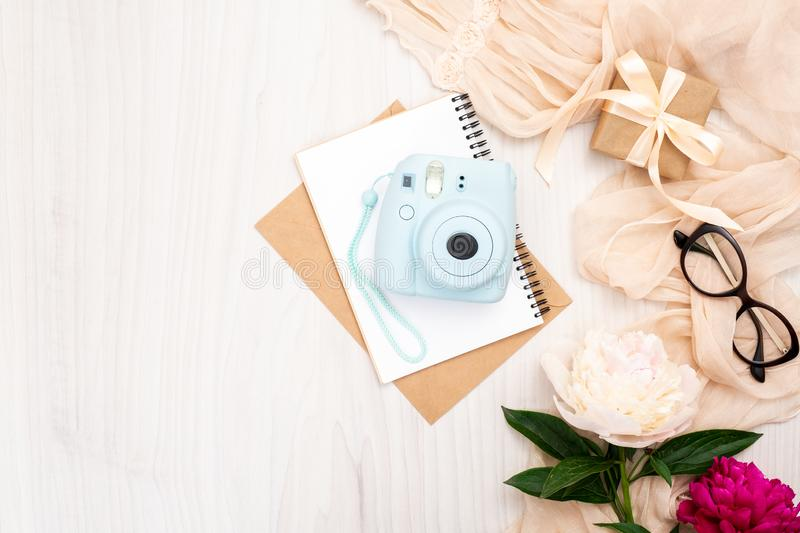 Fashion blogger home office desk with woman items : modern instant photo camera, paper notepad, beige scarf, peonies flowers, royalty free stock photo
