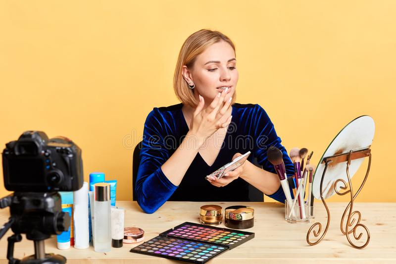 Fashion blogger shares makeup hacks with followers, applies eyeshades on lips. Successful popular young fashion blogger girl sharing makeup hacks with followers royalty free stock image