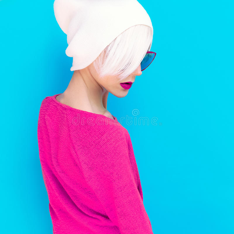 Fashion blond model with trendy cap and sunglasses on a blue background royalty free stock images
