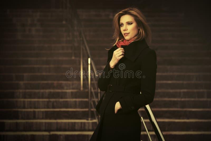 Fashion blond zakenvrouw met een zwarte jas die op de straten van de stad loopt stock afbeeldingen