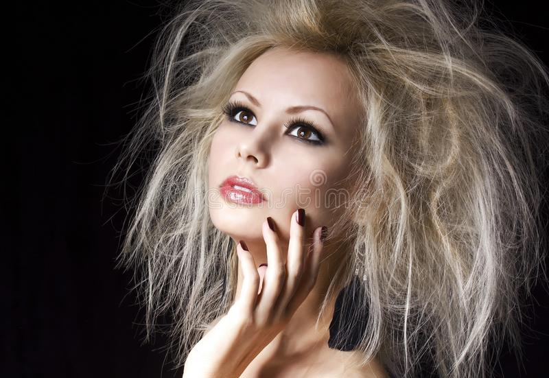 Fashion blonde girl. Beautiful blonde woman with professional makeup and humidity hair style, over black. Vogue model royalty free stock images