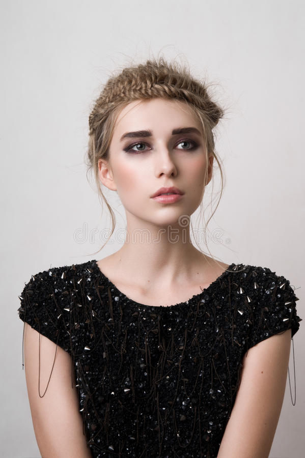 Fashion blonde model with black dress looking away royalty free stock image