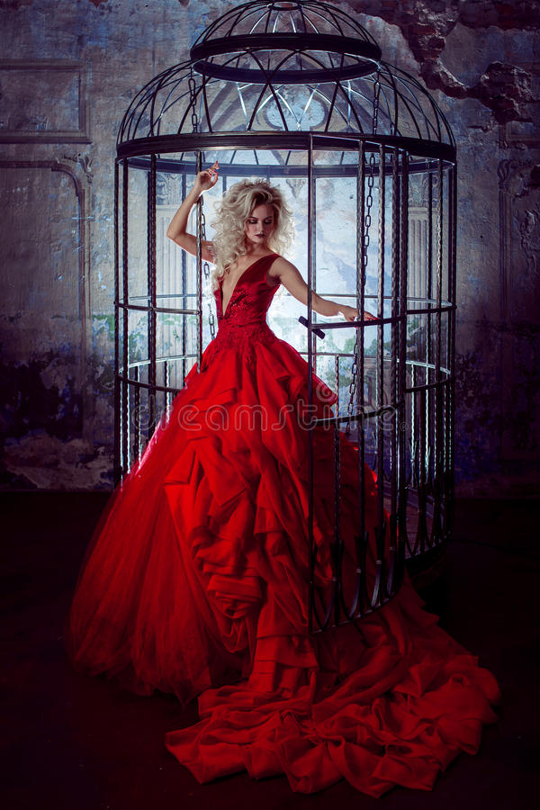 Fashion blonde in red dress with fluffy skirt near the birdcage, concept of liberation stock images
